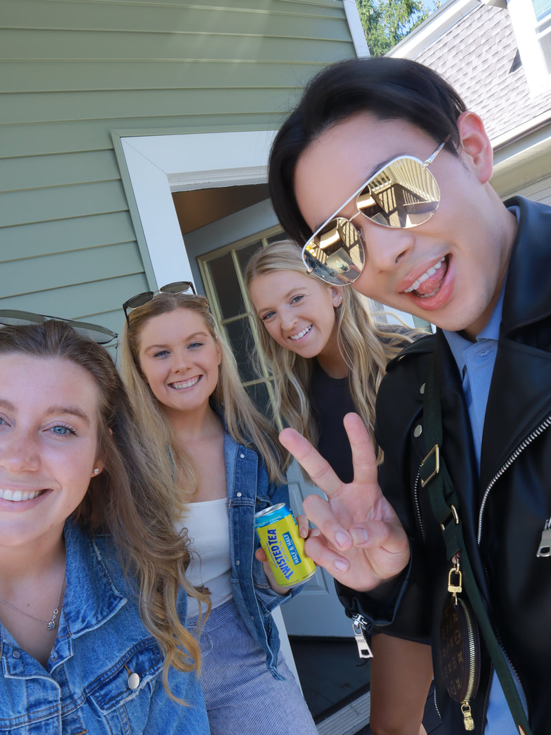 Picture of 3 young women and one man. The man to the right is wearing aviator sunglasses from Quay Australia.
