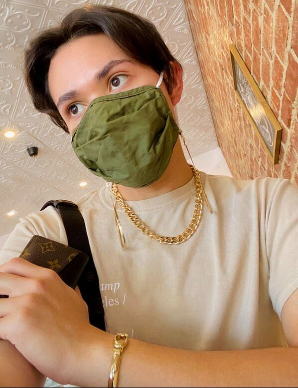 Person wearing a stylish face mask chain accessory on a green old navy face mask